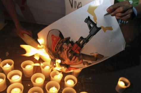 A protester burns a caricature of Libyan leader Muammar Gaddafi during a demonstration in front of the Libyan Embassy in Managua